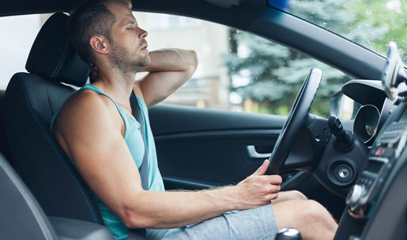 man sitting in drivers side holding his neck in pain