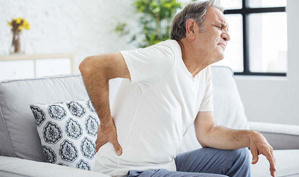 Man sitting on couch holding his back in pain