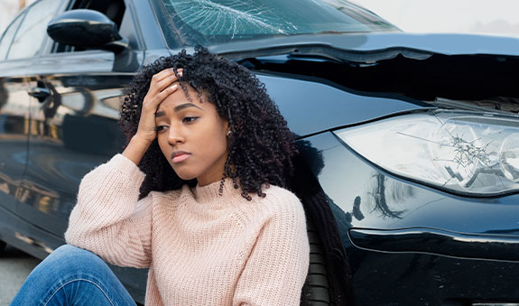 Woman sitting out side of recked car with worried expression