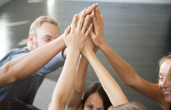 group of people placing hand in the circle